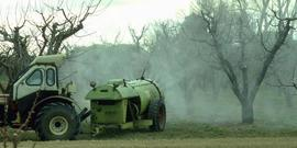 An air-blast orchard pesticide sprayer in operation in an apple orchard.