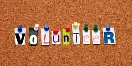"letters forming the word ""volunteer"" on a cork board"