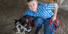 A 4-H member posing with his pig at the Hemlock Fair.