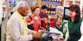 An older adult man purchasing groceries with SNAP Benefits.  