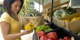 This photograph depicts a woman shopping at a mobile produce market, making healthy food choices from an array of fresh fruits and vegetables.