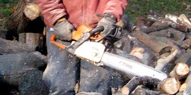 man using a chain saw, wearing protective pants.