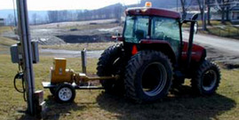 "Photo of tractor and generator, taken from the ""Safe Operation of Emergency Generators"" fact sheet resource."