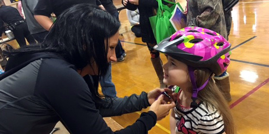 Youth getting bike helmet properly fitted during Safety Fair