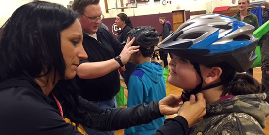 Youth getting helmet fitted to head during Safety Fair
