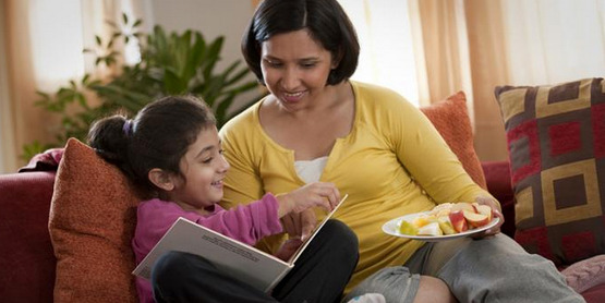 A woman and her daughter read and share a snack together.