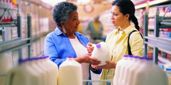 Two women at a supermarket discuss a milk label