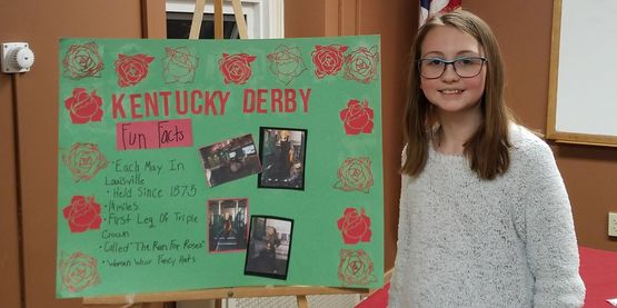 A 4-H Member standing next to her Public Presentations display board about the Kentucky Derby.
