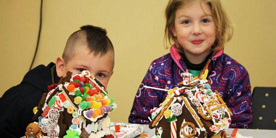 4-Hers posing with finished gingerbread houses