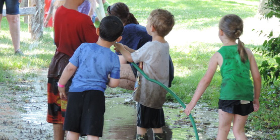 kids playing with the hose in a mud puddle on mud day