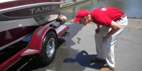 Dan Munsell checks a boat for signs of hydrilla at Treman Marine State Park, Ithaca NY, summer 2013