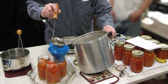 Putting hot tomatoes into a sterilized canning jar for hot water bath processing.