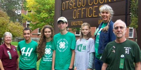 4-H youth and adults stand before Otsego County sign.