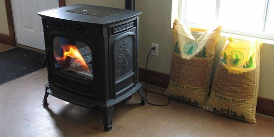A wood pellet stove in operation with bags of fuel (right)