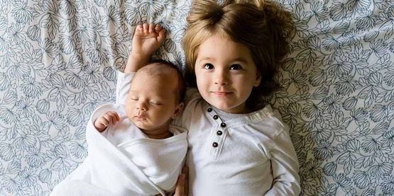 young girl with infant sibling