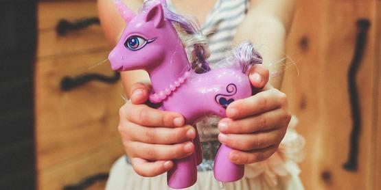 girl holding a toy unicorn