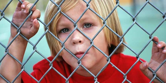 boy looking through a chain link fence