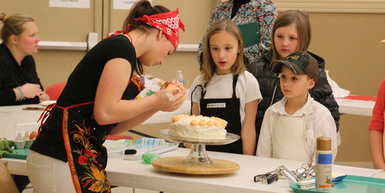 4-Hers watching another member decorate a cake.
