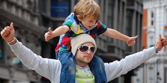 young boy on man's shoulders in city, both giving thumbs up signal