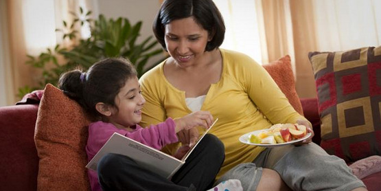 A woman and her daughter read and share a healthy snack together.