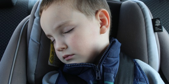 A toddler napping cozily in a car.