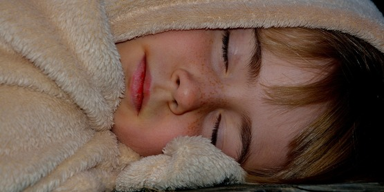 A child sleeping with her blanket