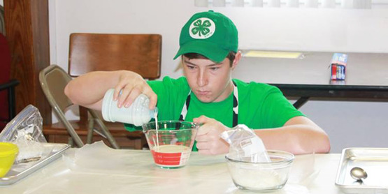 A 2015 PINY participant measures milk for his recipe!