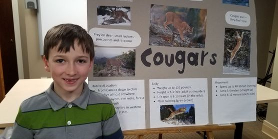 A 4-H Member standing next to his Public Presentations display board.