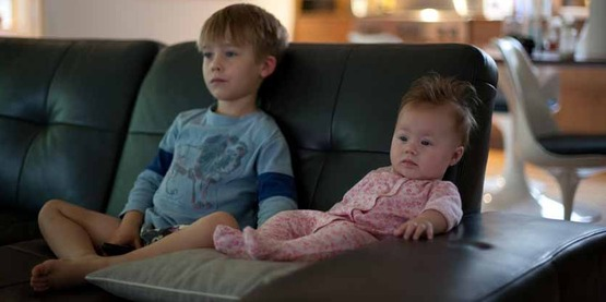 Young boy and a baby on the sofa watching Netflix