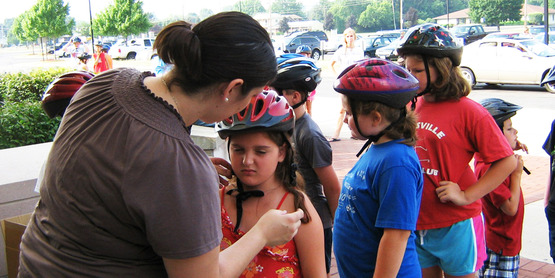 Local children having their helmets checked for proper fit.