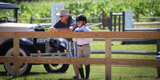 young rider with grandfather watching the event