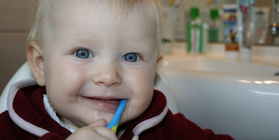 A baby brushing his teeth