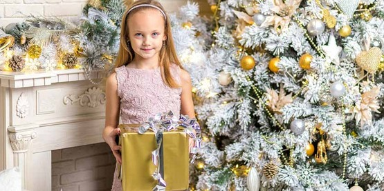 girl with present in front of a Christmas tree