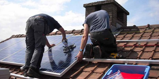 Two men on a roof installing solar panels.