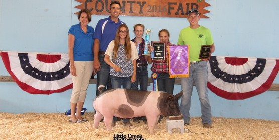 Corinne Covert with her Grand Champion Hog. Photo by Little Creek Photography.