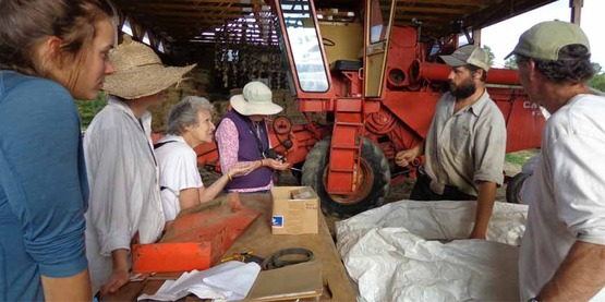 Ag photo of people in a barn with a tractor, from the old website