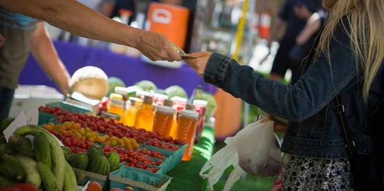 customer receives change from a farmer at a 2016 farmer's market held by the Dilmun Hill student farm, Cornell University