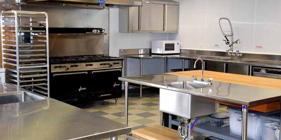 2 oven/10 burner commercial stove with fire suppression hood, and two stainless steel islands with prep sinks