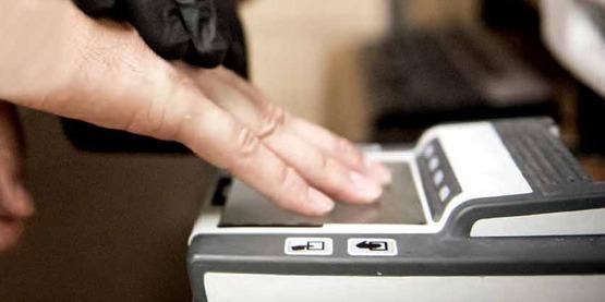 United States Marshals fingerprinting a prisoner.