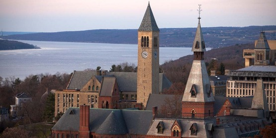 Central campus in fall, with Sage Hall, McGraw Tower, and Cayuga Lake in the background.