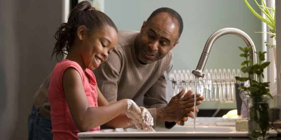 African-american father teaches his young daughter about washing her hands CDC Photo #11286 - in the public domain