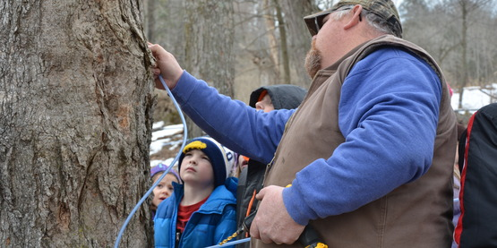 Charlie teaching the After School kids about taping trees to make Pure Maple Syrup!