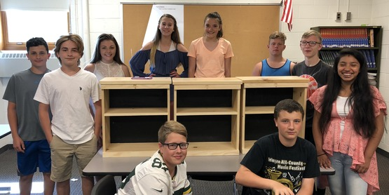Clyde-Savannah tech students with one of their bookshelves, created with teacher Matt Drahms