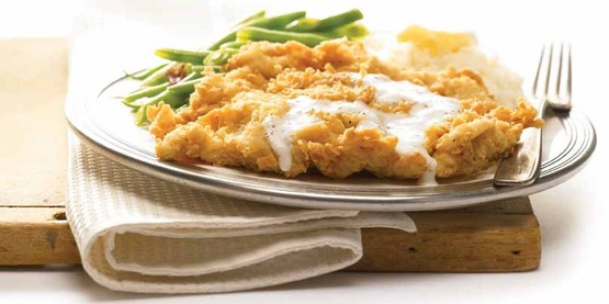 a plate with fried chicken, gravy, biscuit, green beans