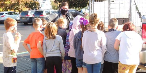 Educator speaking to children about turkeys prior to Thanksgiving.