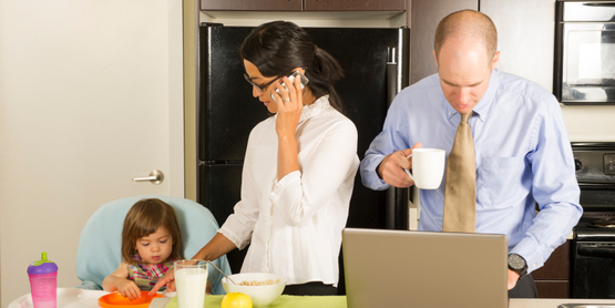 family having breakfast while using technology