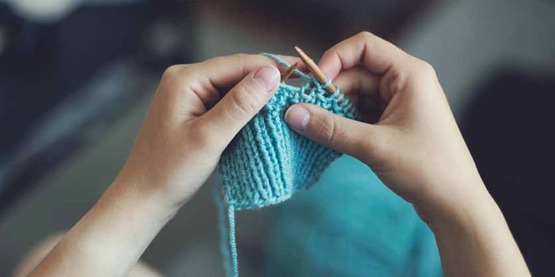 hands of a young child knitting,