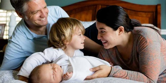 Family group of father, mother, small child and infant, on bed