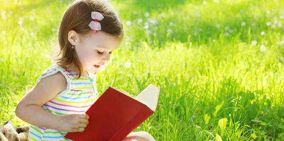 small girl reading in a field