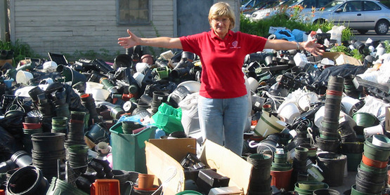 Monika Roth, Agriculture Program Leader at CCE-Tompkins, stands among plastic pots and trays brought in for recycling at the first Gardener's Pot Swap recycling event in June 2008.
